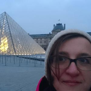 Lena na tle piramidy w Luwrze
