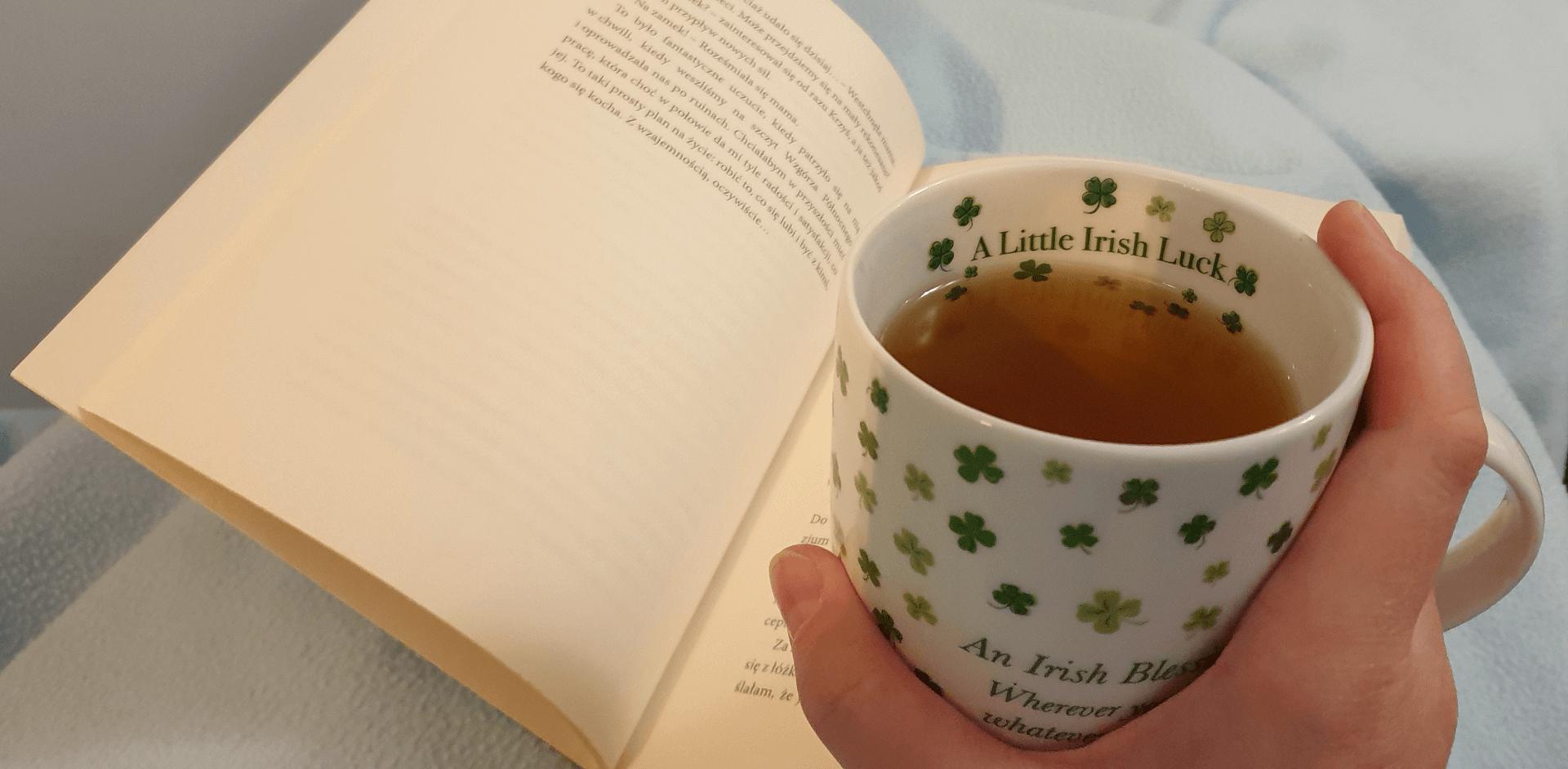 """Książka """"Przeczucia"""" z kubkiem w koniczynki z napisem o szczęściu irlandzkim"""